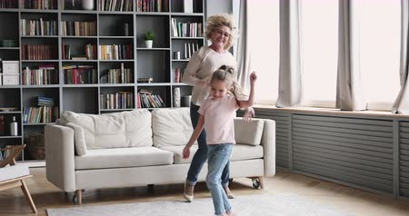 muziekfeest : Funny small girl granddaughter dance with old grandma babysitter in living room, happy two 2 generations active family senior nanny and cute energetic grandkid jump play enjoy time together at home