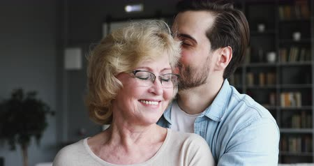 milující : Caring young man grown adult 30s son hugging kissing happy smiling older mature 60s mom expressing affection, care and love concept embracing middle aged mother cuddling visiting elderly parent
