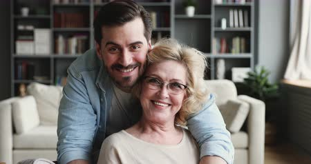 milující : Smiling 30s young adult man grown handsome son looking at camera hugging old mature 60s mom expressing love and care embracing cuddling on mothers day concept, 2 generations family closeup portrait