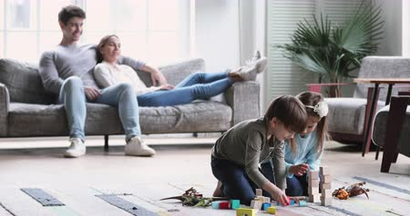 descontraído : Two cute kids playing on floor sit on carpet while relaxed young parents couple lounge on sofa in modern apartment living room interior, family with children enjoying leisure time activities at home