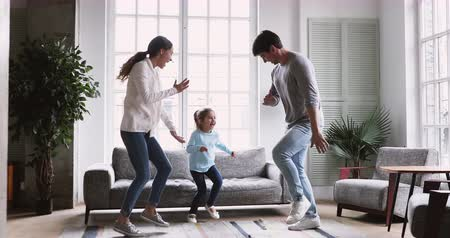 den matek : Happy playful young family couple dancing with cute active preschool small child daughter in living room interior together, adult parents mum dad and kid girl pretending running having fun at home
