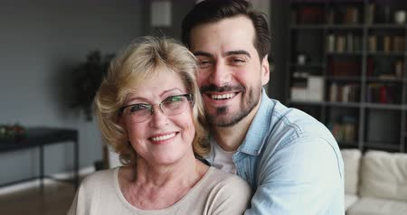 den matek : Happy affectionate older mom and adult son embracing smiling looking at camera, relaxed millennial young man hugging loving 60s mother posing for 2 two age generations family closeup portrait indoors