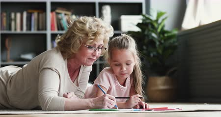 koncentracja : Older mature 60s grandmother babysitter teach cute preschool granddaughter draw colored pencils lying on carpet floor, happy senior grandma teacher help playing creative activity with gradnkid at home