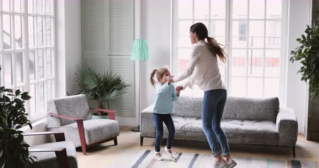 den matek : Happy young adult parent mum and small child daughter jumping having fun in living room, active cheerful baby sitter mother dancing with cute kid girl at home enjoy leisure activity together at home