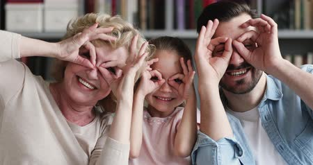 três pessoas : Funny multigenerational 3 three generations family portrait, happy old grandma mother, cute small child girl daughter grandchild and young grown son adult father make binoculars laugh look at camera