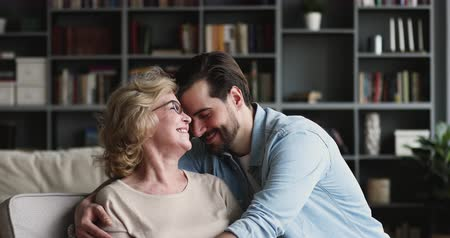 together trust : Grateful loving young adult man grown-up son embracing mature older elderly mum visiting retired parent at home, happy two age generations family hugging expressing tenderness, respect and care concept