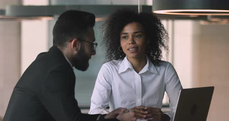 estagiário : Smiling young african ethnicity female office worker nodding, agreeing with arabian male coworker. Focused biracial woman listening to arabic financial advisor trainer mentor lawyer coach at meeting.