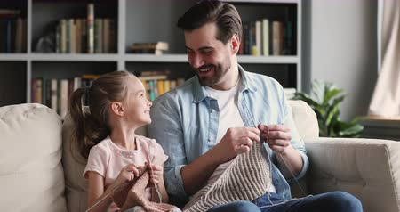 babysitter : Happy family young adult father having fun teaching little cute preschool daughter learn knitting needles, smiling parent dad with funny small child girl laugh enjoy craft hobby sit on sofa at home