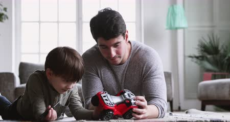 любопытство : Young adult dad teaching cute preschool son hold screwdriver help father pretend repairing toy fixing truck together, happy family parent daddy and little boy playing toy car lying on carpet at home