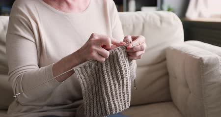 eski moda : Old adult woman holding needles knitting knitwear scarf relaxing on sofa, senior mature lady elder grandma female hands doing handicraft handwork hobby concept sitting on couch at home, close up view