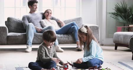 leisure time : Cute preschool children playing wooden blocks together sit on floor carpet and their young adult parents relaxing on sofa spending free weekend family time in modern living room interior at cozy home