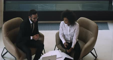 контракт : Top view young arabian businessman discussing project ideas with involved african american businesswoman, showing application on computer. Successful mixed race people establishing partnership. Стоковые видеозаписи