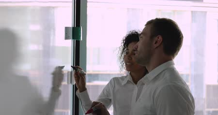 speaker : Focused young caucasian male company employee working near white board with african american female colleague. Diverse coworkers holding markers, writing notes on flip chart, preparing for conference.