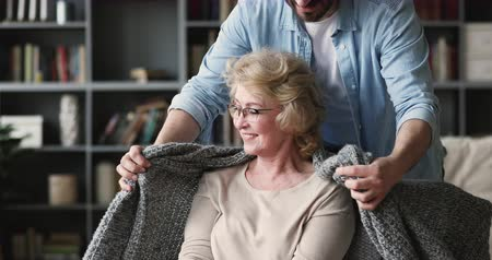 middle : Caring affectionate young adult man grown son coming to mature middle aged mother sit on chair covering older parent with warm plaid blanket hugging relaxed senior mum showing care support at home Stock Footage
