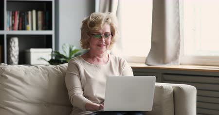 nagymama : Smiling older adult woman user typing on laptop notebook sit on sofa surfing internet at home, happy mature 60s grandma wear eyeglasses using computer modern tech device concept relax on couch alone Stock mozgókép