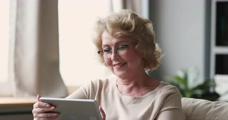 optický : Smiling senior adult 60 years old lady wear optical glasses using digital tablet at home, happy relaxed middle aged woman surfing internet reading online news spend time with modern technology gadget