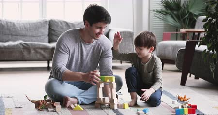 zabawka : Happy young adult parent dad and child son play toys sit on floor carpet at home, caring father having fun help cute kid build tower of wooden blocks enjoy game activity give high five in living room