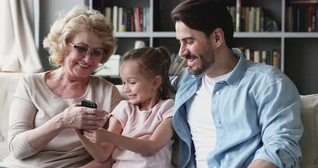 três pessoas : Happy multigenerational 3 age generation family using smart phone mobile gadget sit on sofa, cute small kid granddaughter recording funny video having fun with young adult dad and old grandma at home