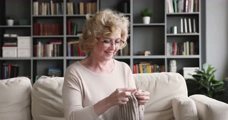 lavoro a maglia : Relaxed mature older woman knitting needles sitting on sofa at home, smiling senior adult retired grandmother knit handmade scarf enjoy leisure hobby handwork craft on weekend in living room at home