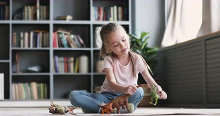 zabawka : Funny cute small kid girl having fun playing dinosaurs alone sitting on carpet, adorable preschool pretty child having fun holding dino toys enjoying leisure playtime imagine activity game at home