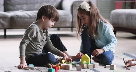 zabawka : Two cute kids preschoolers brother and sister helping building of wooden blocks together sit on floor carpet, 2 friendly small children siblings boy with girl talking playing toys game in living room Wideo