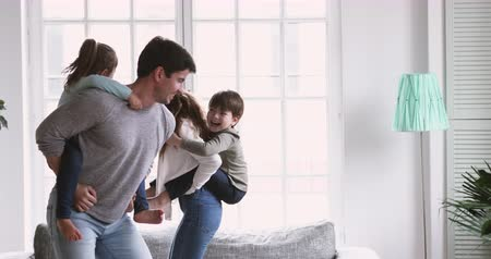 relação : Active funny young adult parents mum dad playing with two children give small cute kids piggyback ride at home, happy family of four enjoy weekend lifestyle game having fun in living room together