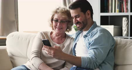 gepensioneerd : Smiling young adult man grownup son showing funny social media photos enjoying using smart phone mobile apps sit on sofa with older mature parent mom having fun laughing looking at cellphone screen