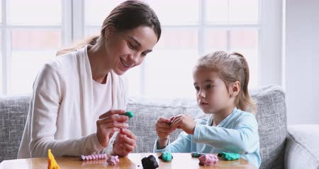 пластилин : Female baby sitter mother teacher helping cute preschool kid girl sculpting playdough together at home, young adult parent mom and small child daughter molding modeling clay toys handcraft activity