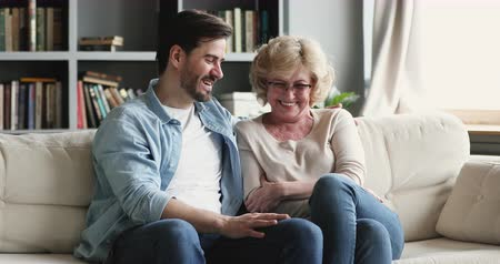 den matek : Cheerful 2 two generations family talking laughing bonding sit on sofa at home, happy older mature parent mother and young adult grown son chatting relaxing having fun on couch in living room together