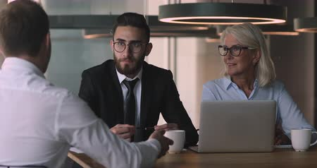 recrutamento : Focused young arabian male and older female hr managers recruiters employers listening to job applicant on hiring negotiation job interview meeting in office, human resources, employment concept. Stock Footage