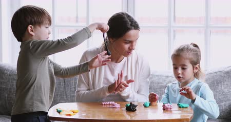 пластилин : Young adult parent mother baby sitter and two small children boy and girl sculpting playdough molding modeling clay at home, happy mom having fun with kids play do creative handcraft activity together