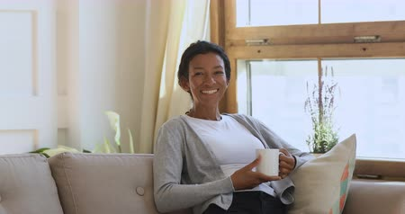 写真 : Happy young african american girl resting on comfortable sofa, holding mug of hot coffee, posing for photo video portrait at home. Pleasant attractive positive biracial woman looking at camera.