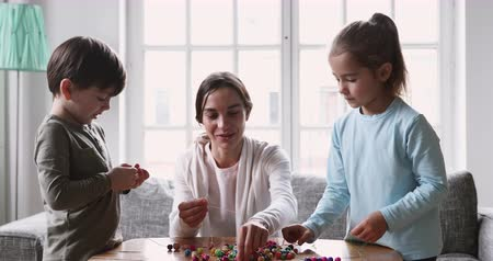 koncentracja : Smiling young adult mum baby sitter nanny teach two small kids daughter and son make necklace hold beads and cord play sensory game together having fun doing handicraft activity sit on couch at home Wideo
