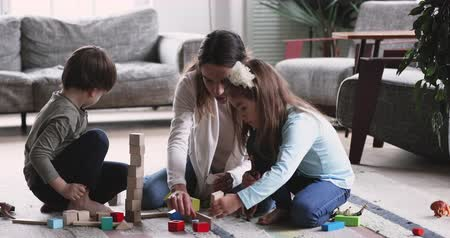 zabawka : Happy young adult mother nanny playing with two cute small kids having fun sit on floor carpet at home, playful mum nursemaid helping preschool children building tower of wooden blocks in living room