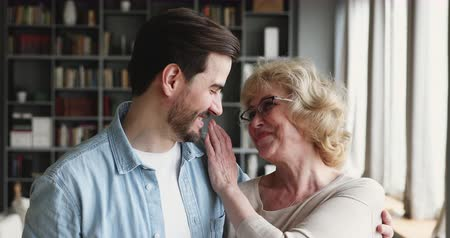 neşeli : Happy middle aged older woman mother and young adult son laughing bonding looking at camera, loving parent mom embracing grown man standing at home, 2 two age generations family friendship, portrait