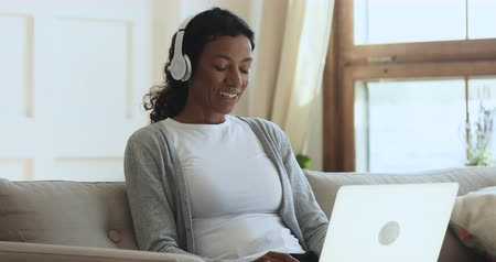 общаться : Smiling young african american woman wearing wireless headphones, holding video call with relatives using computer. Happy millennial biracial girl chatting online with friends, sitting on couch.