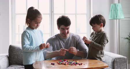 zabawka : Happy young father help cute focused preschool small children boy and girl do craftwork play together learn make handmade multicolored beads necklace having fun enjoy sensory motor activity at home