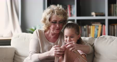 говорить : Loving older mature adult grandmother teaching little cute girl granddaughter knitting together, 2 two generations family grandparent and grandchild enjoy leisure hobby having fun sit on sofa at home Стоковые видеозаписи