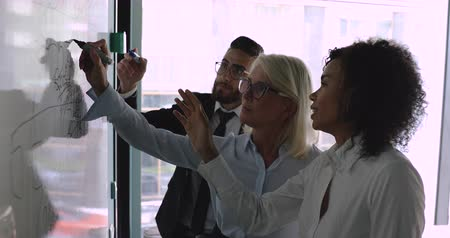 warsztat : Focused middle aged female leader in eyeglasses holding markers, writing notes, preparing for presentation, managing working process on whiteboard with motivated multiracial employees in office.