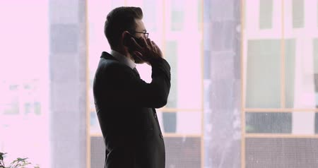 hívó : Focused confident young arabic male manager dialing phone number, calling to client. Concentrated middle eastern ethnicity millennial businessman talking on mobile phone, looking at window in office.