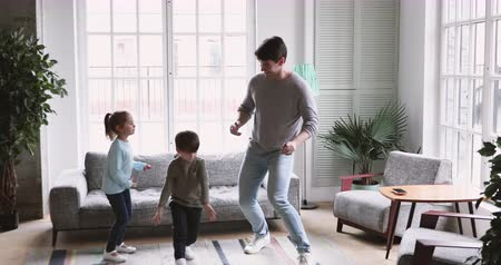 três pessoas : Cute funny small kids imitate young adult father funny moves dancing in living room together, happy family dad babysitter and two active energetic preschool children having fun at home play together