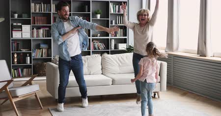 três pessoas : Happy funny multigenerational family 3 age generations having fun dance together in living room, cute girl daughter granddaughter, old grandmother and young son father enjoy lifestyle activity at home