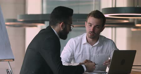konsultant : Happy young caucasian businessman discussing online project presentation with smart arabian male partner in office. Confident salesman financial advisor explaining deal details to arabic client.