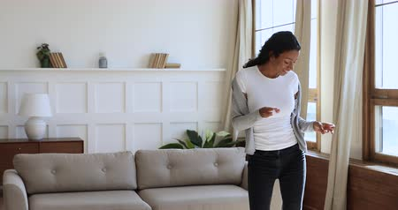 immobilien : Carefree young mixed race girl having fun at new own apartment alone. Cheerful millennial african ethnicity woman dancing to favorite music, enjoying freedom in living room, active lifestyle concept.
