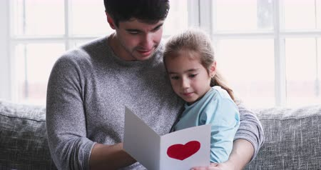 milující : Happy young dad hugging cute adorable small child daughter learn reading postcard with red heart congratulating parent on fathers day embracing daddy holding greeting card sit in living room on sofa Dostupné videozáznamy