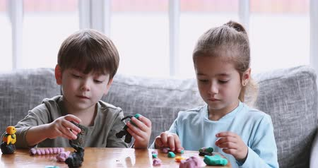 mold : Two cute preschool children siblings making toys sculpting playdough on table sit on sofa at home, 2 focused adorable kids boy brother and girl sister playing molding colorful modeling clay together Stock Footage