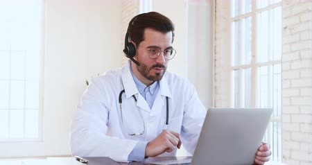 lekarstwa : Professional male doctor wear white medical coat and headset making conference call on laptop computer consulting help distance patient client online in video chat explain treatment by webcam concept