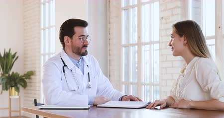 醫療保健 : Qualified man doctor physician wear white coat stethoscope consult young adult woman patient client explain diagnosis treatment at checkup visit sit at desk in medical office, women healthcare concept