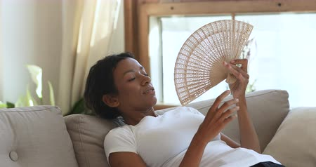 etnia africano : Overheated young african american lady suffering from high temperature indoors or hot summer weather. Exhausted sweaty millennial biracial woman waving fan, cooling herself, no air conditioning.