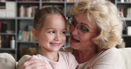 foster : Happy loving older mature adult grandma hug cuddle small cute kid granddaughter look at camera, two generations grandparent and grandchild bonding embrace enjoy affectionate moment, closeup portrait Stock Footage